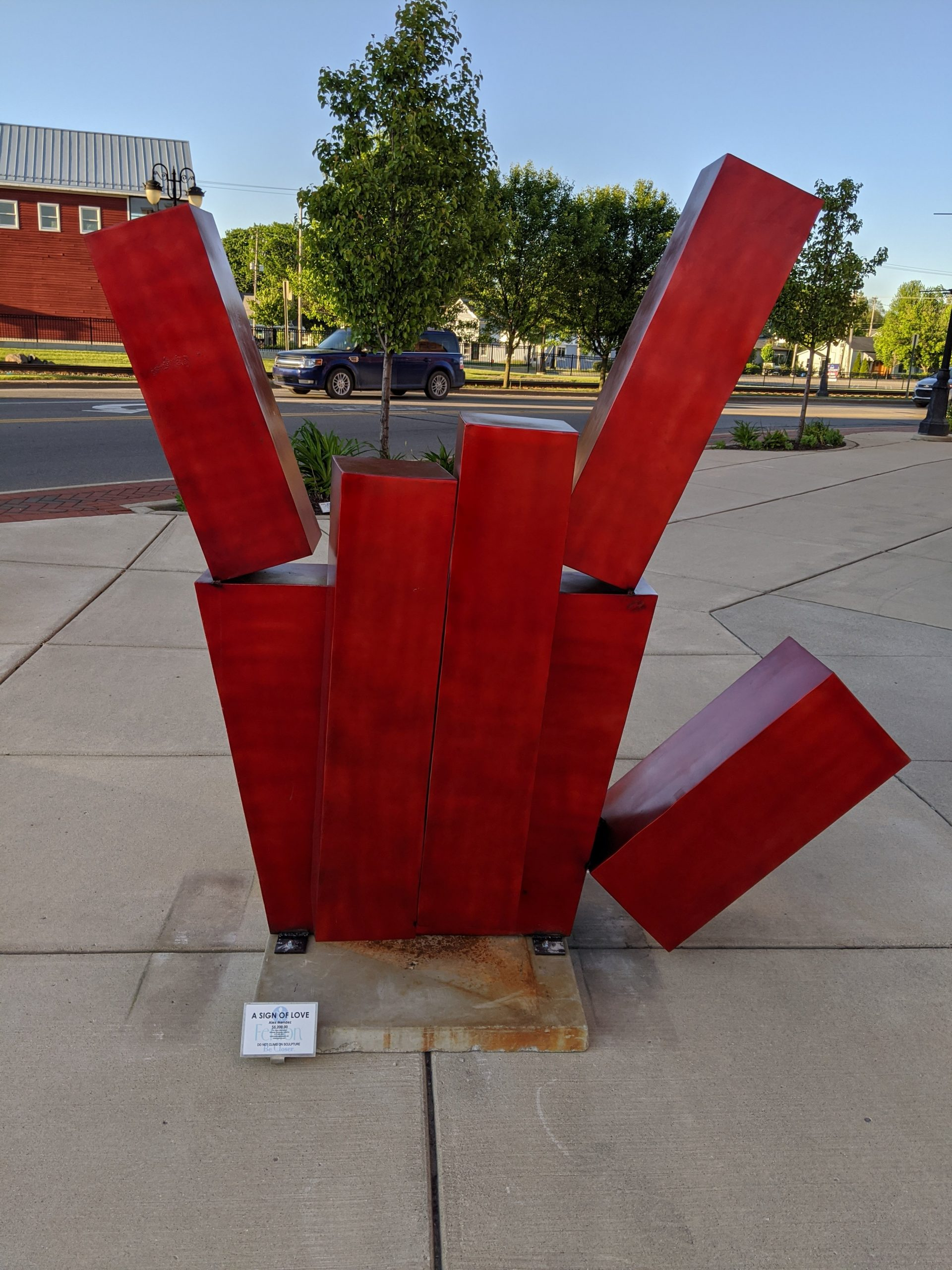 "Picture of red sculpture shaped like the handshape for ""love"" ASL"